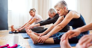 photo of elderly people sitting on yoga mats stretching